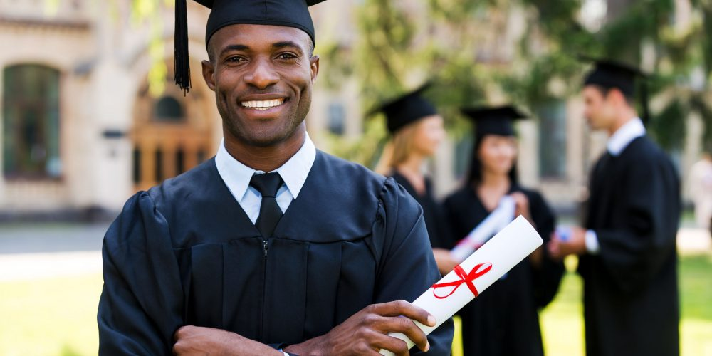 Happy graduate. Happy African man in graduation gowns holding diploma and smiling while his friends standing in the background